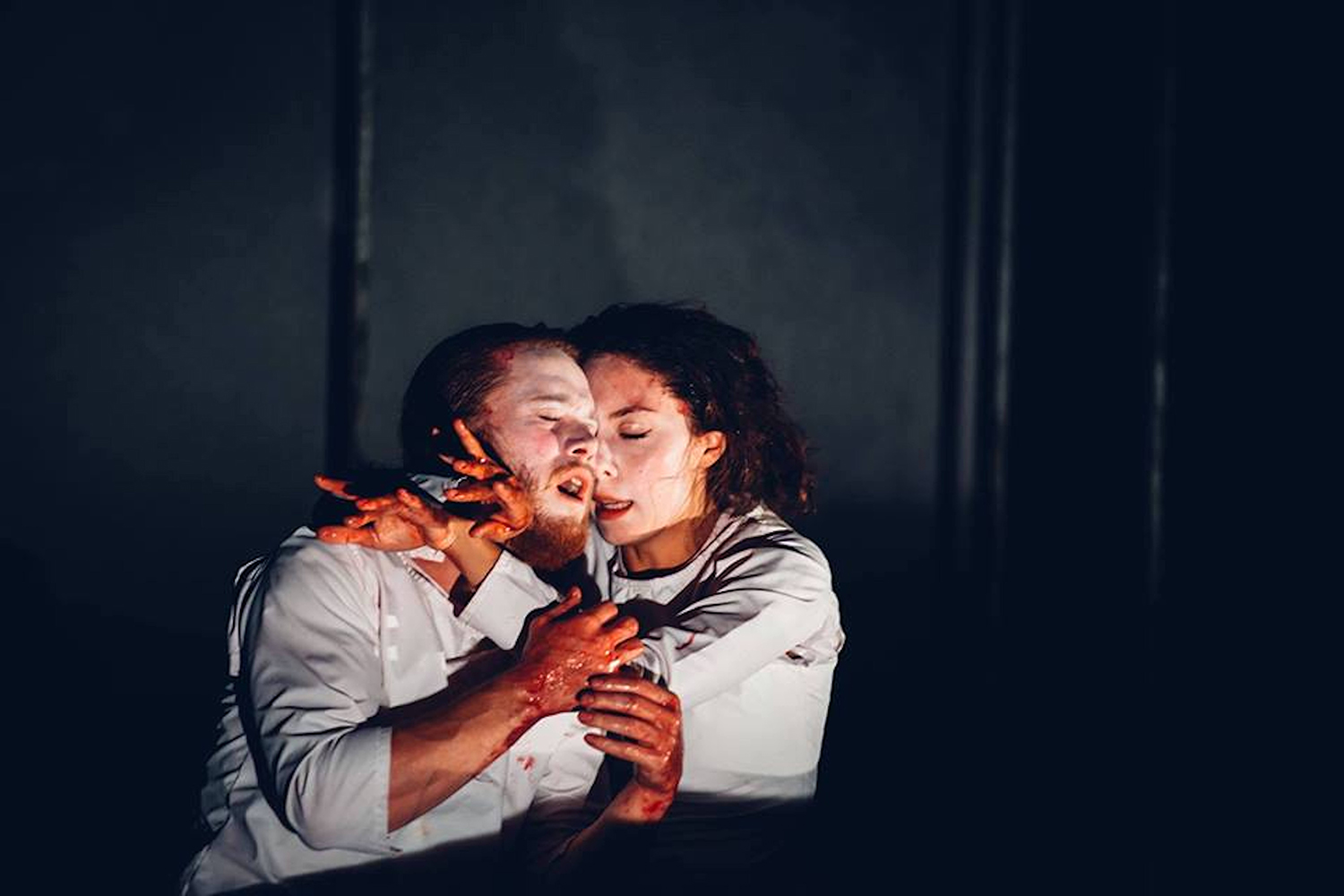 Macbeth and Lady Macbeth embrace with blood-stained hands.
