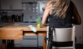 A female soldier sits at a kitchen table with an automatic weapon behind her.
